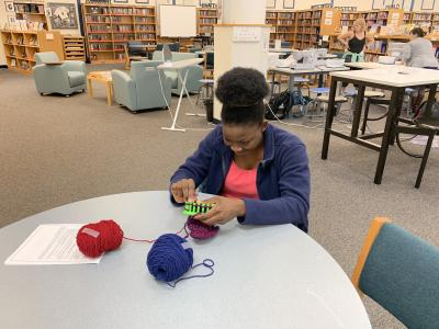 "Student knitting for ""Hats for Some"""